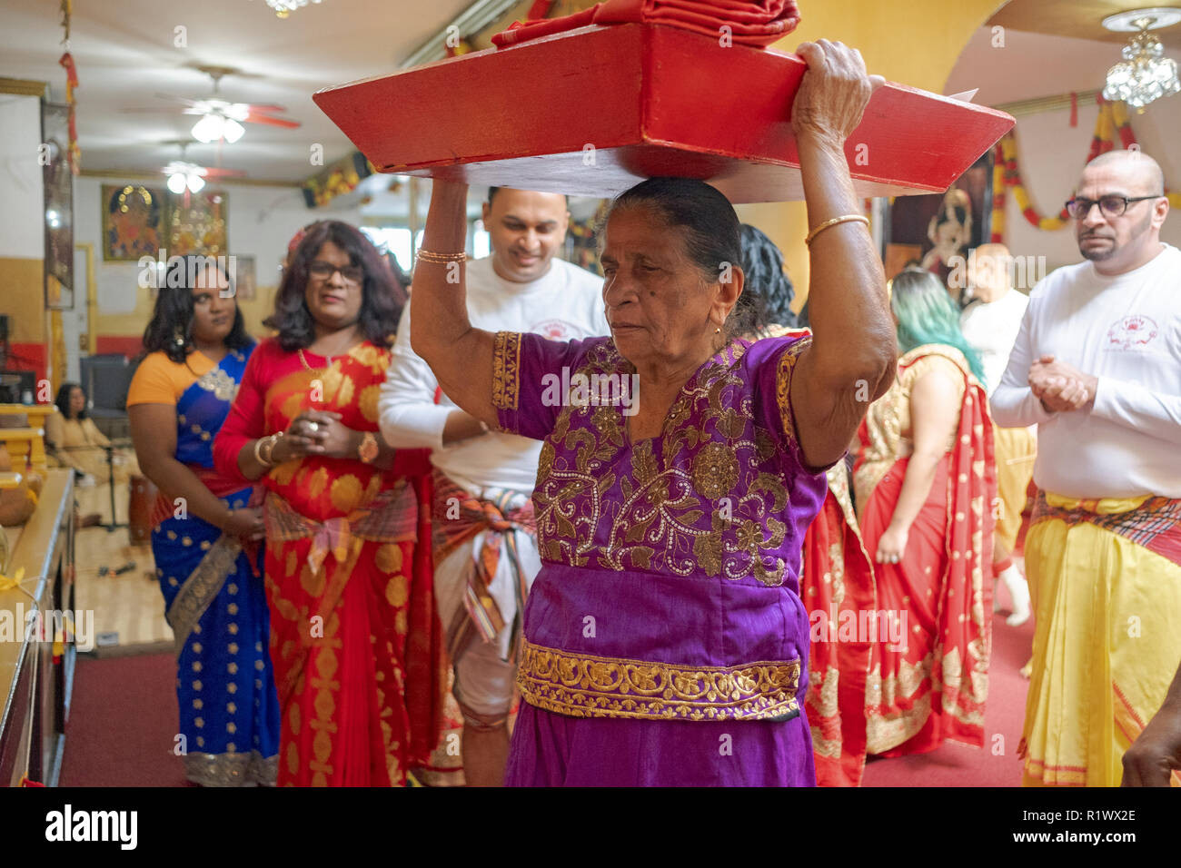 Surrounded by her family, an older Hindu woman brings offerings to the deities at a temple in Ozone Park, Queens, New York. - Stock Image