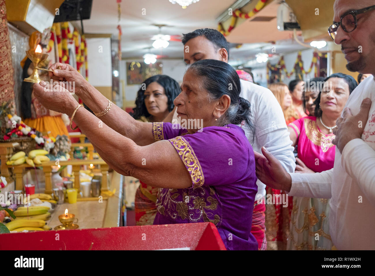 Surrounded by her family, an older Hindu woman makes offerings to the deities at a temple in Ozone Park, Queens, New York. - Stock Image