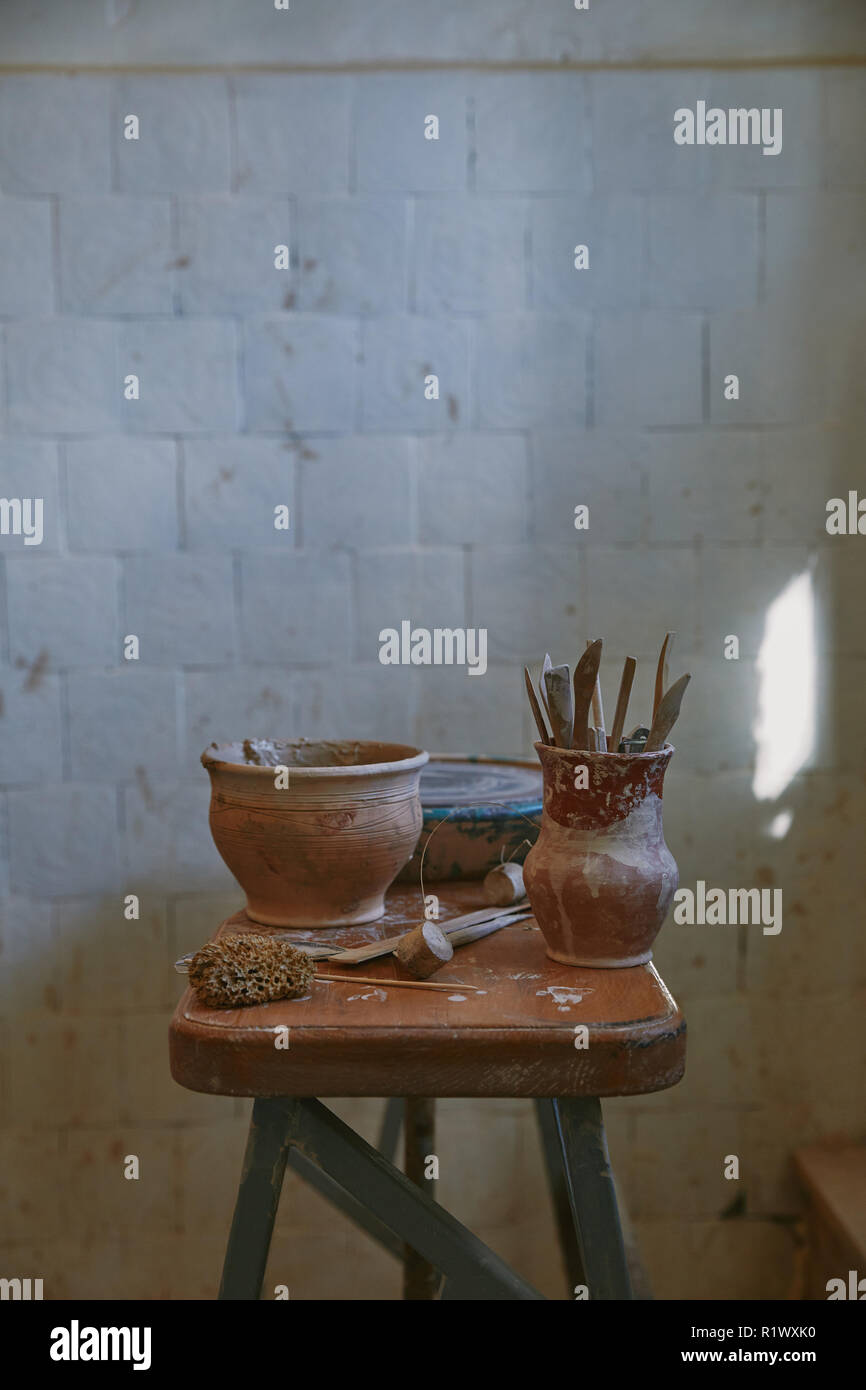 selective focus of pottery tools at table in pottery studio - Stock Image