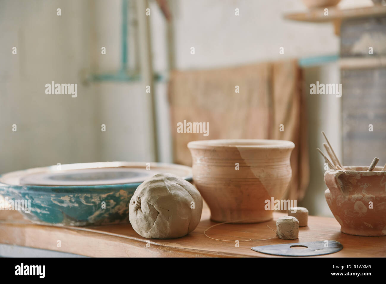 selective focus of clay and pottery tools at table in workshop - Stock Image