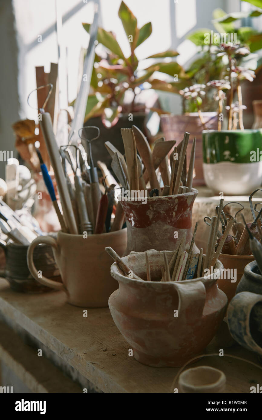 selective focus of pottery tools and paintbrushes at table in pottery studio - Stock Image