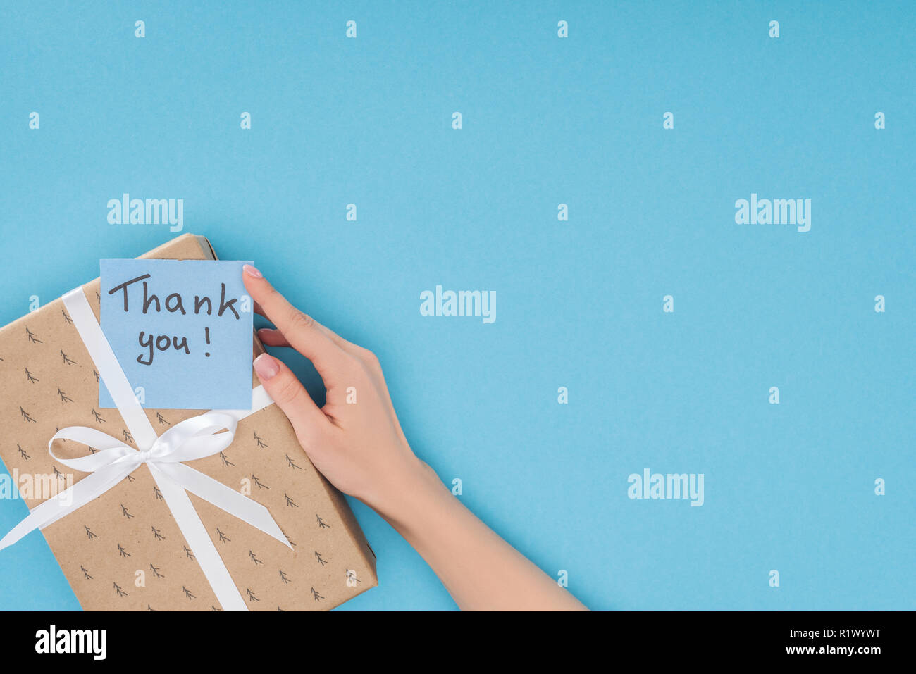 cropped view of hand and sticky note with thank you lettering on gift box isolated on blue background - Stock Image
