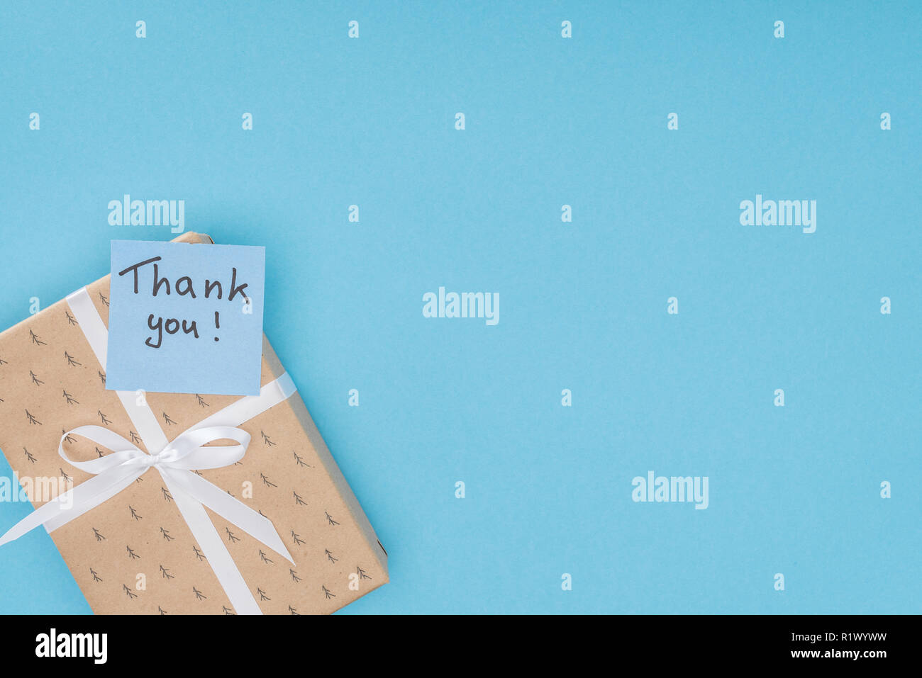 sticky note with thank you lettering on gift box isolated on blue background - Stock Image