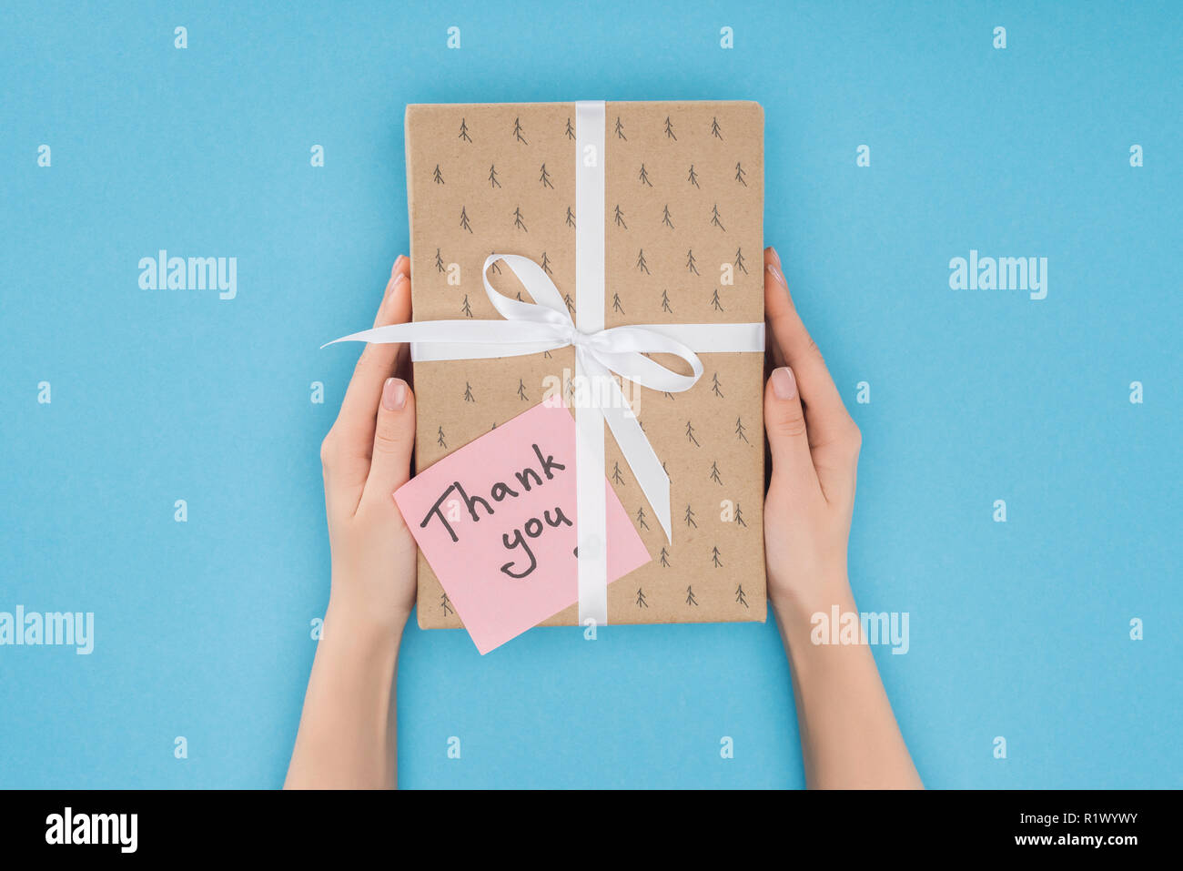 cropped person holding gift box with sticky note with thank you lettering isolated on blue background - Stock Image
