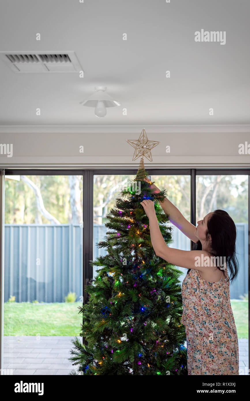 Woman decorating australian Christmas tree in her house, South Australia - Stock Image