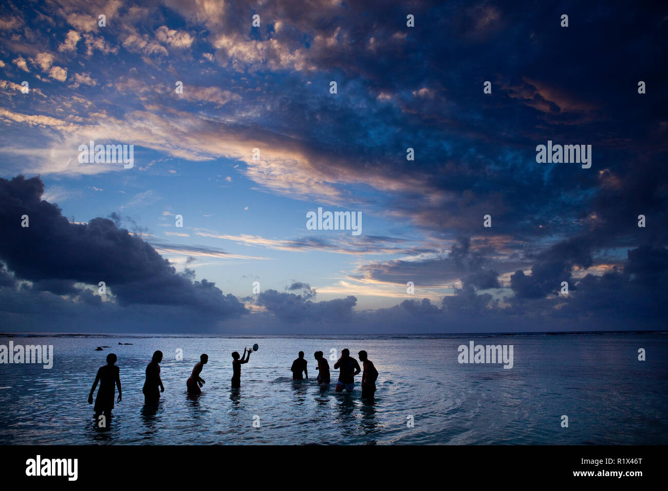 Locals cooling off with some lagoon rugby, Rarotonga, Cook Islands. - Stock Image