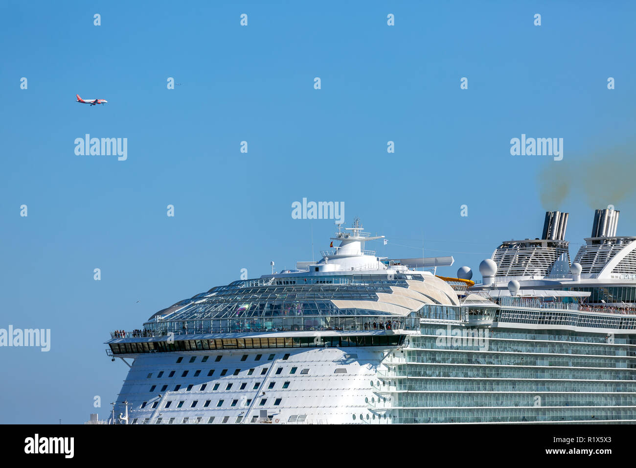 Spain, Barcelona, July 8th -2018, a luxury cruiser ship and a landing aircraft at Barcelona Harbor - Stock Image