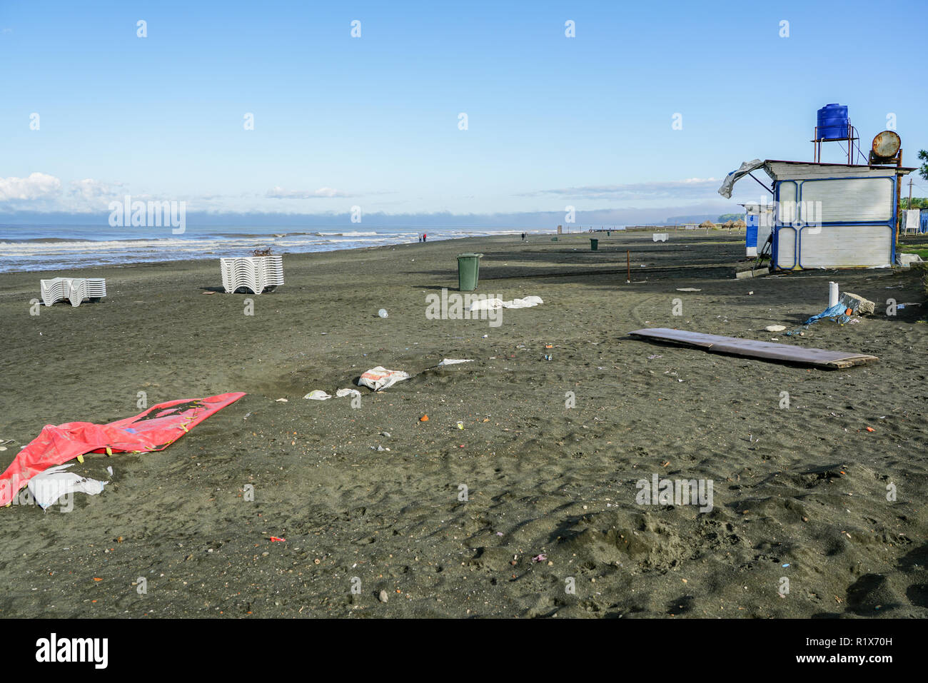 dirty black sand beach after the end of the tourist season - Stock Image