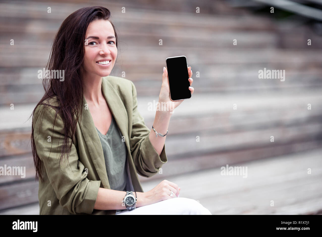Happy woman with smartphone outdoors in the city - Stock Image