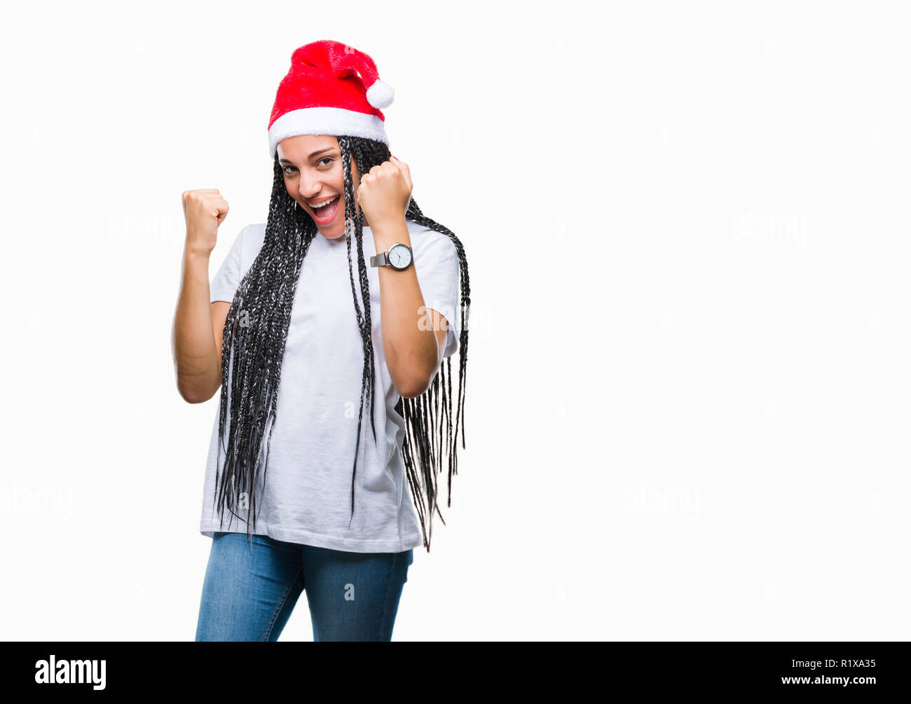 Young braided hair african american girl wearing christmas hat over isolated background very happy and excited doing winner gesture with arms raised,  - Stock Image