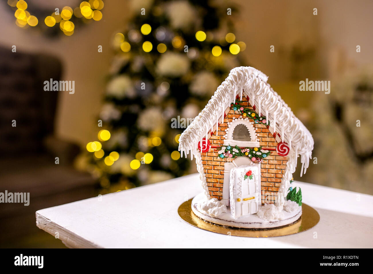 Gingerbread House In Front Of Defocused Lights Of Christmas