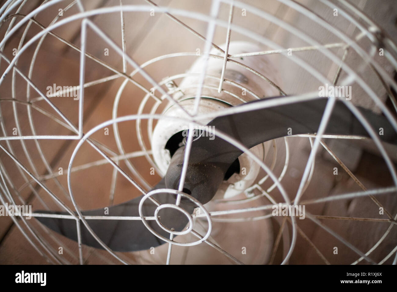 old mid-century metal fan on a wooden farm table - Stock Image