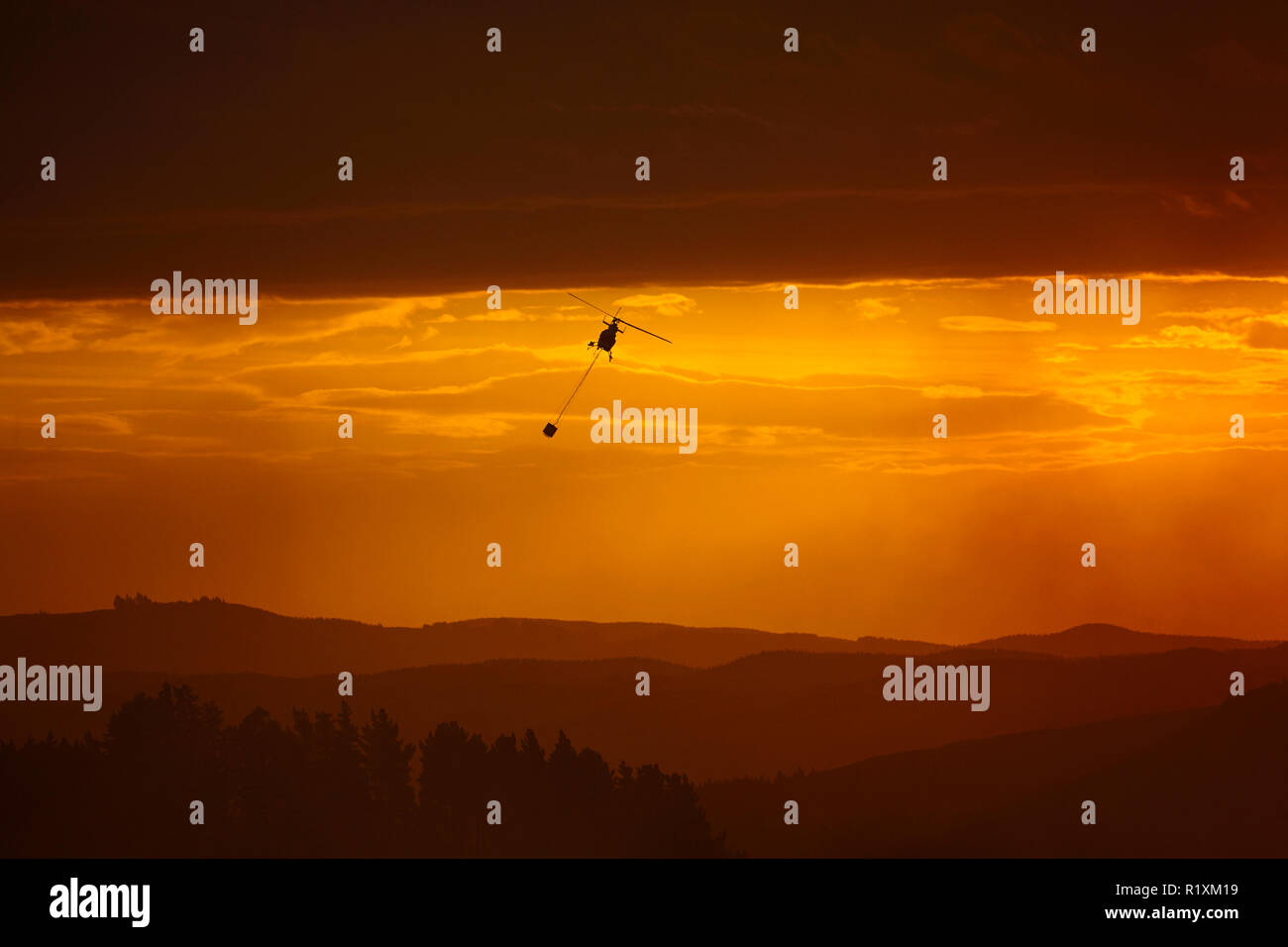 Smokey sunset and helicopter fighting fire at Burnside, Dunedin, South Island, New Zealand - Stock Image