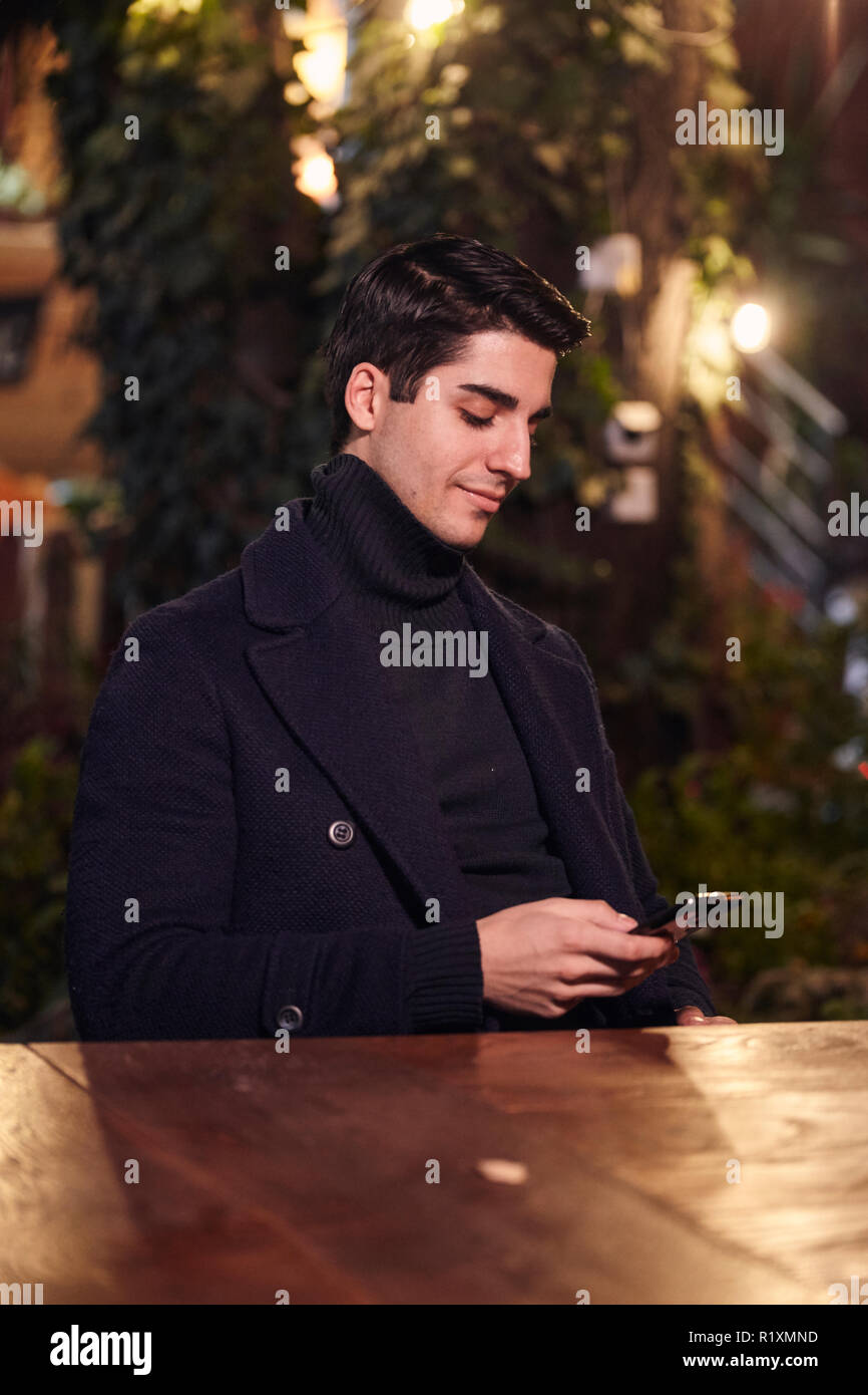one young handsome man, sitting in cafe garden at night outdoors, texting using smartphone. Stock Photo