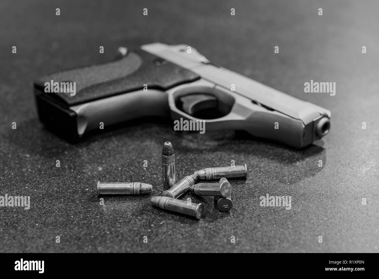 Bullets and Handgun on Black Table - Stock Image
