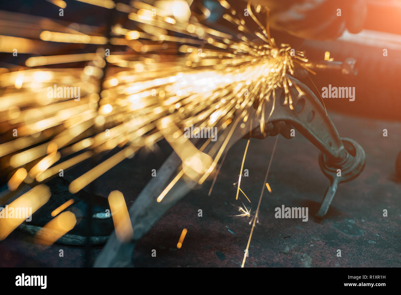 Proffecional worker repair car part with angle grinder. Many sparks on background. - Stock Image