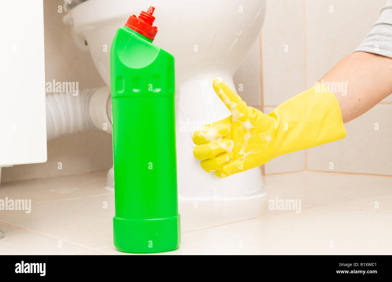 Yellow latex glove with thumb up as recommend gesture for green bottle cleaning product - Stock Image