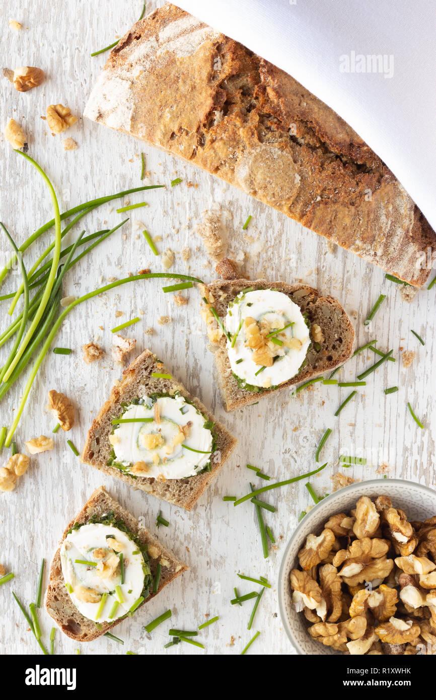 Frisches Landbrot und Schnittchen mit Frischkäse Schnittlauch und Walnüssen auf hellen Holzuntergrund - Stock Image