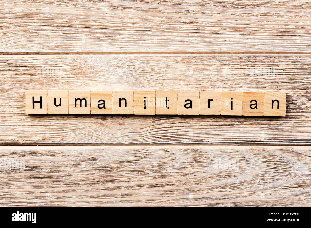 humanitarian word written on wood block. humanitarian text on table, concept. - Stock Image