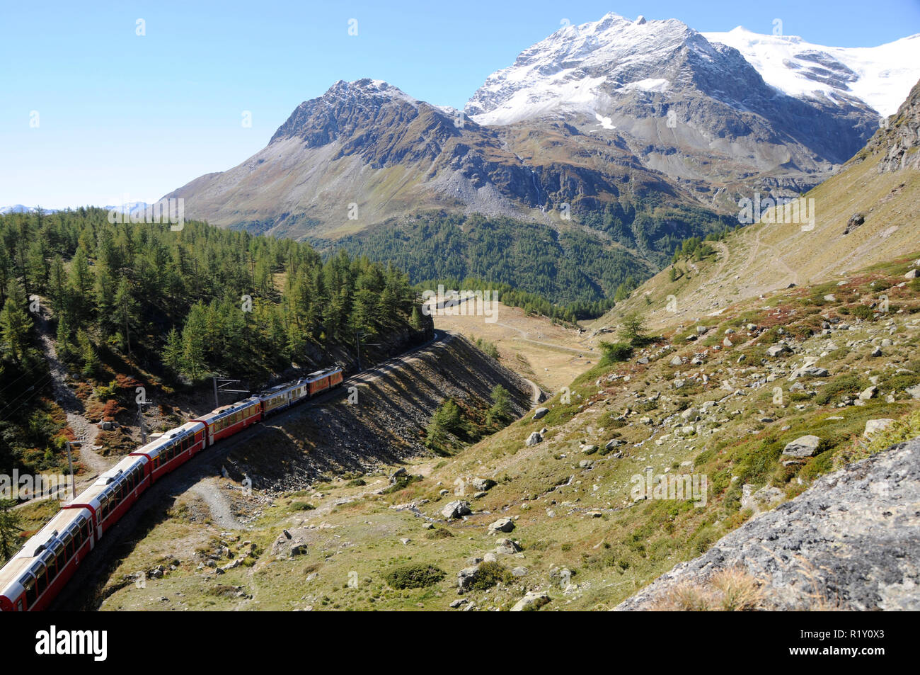 The Bernina train drives over the Swiss Alps in the Oberengadin from Pontresina via Bernina-Hospitz to Alp Grüm and ends in Tirano (Italy). - Stock Image