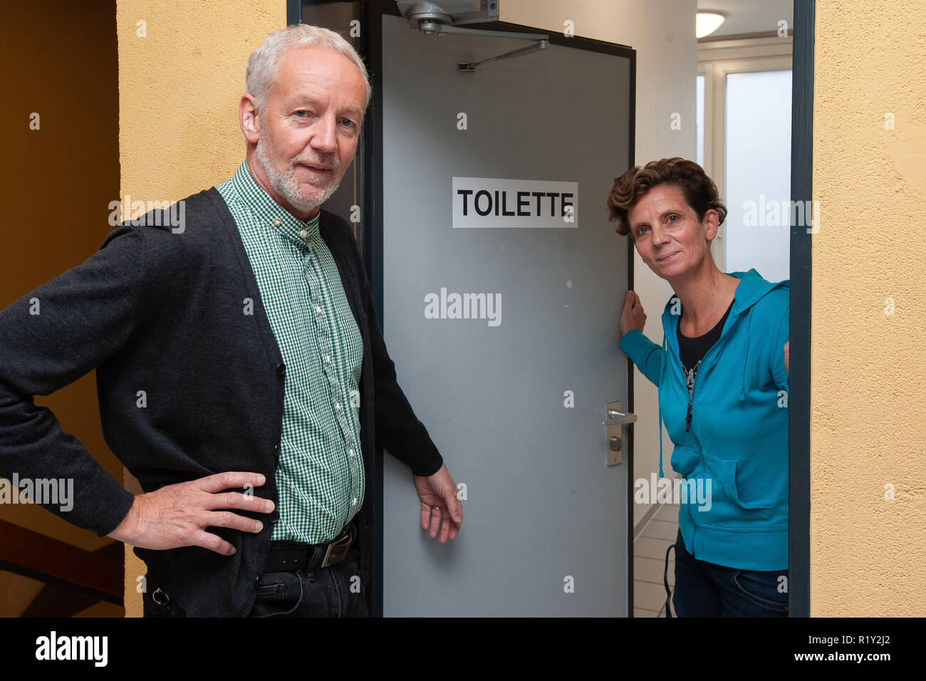 26 October 2018, Lower Saxony, Göttingen: Georg Bartelt, headmaster at Hainberg-Gymnasium, and Sandra Wolf, trusted teacher at Hainberg-Gymnasium, are standing at the door of a unisex toilet or an all-gender toilet in the school building. Two toilet rooms of the school, formerly one for boys and one for girls, were provided with the stroke 'Toilette' and prepared for the pupils, who do not find themselves in a classical gender order. Photo: Swen Pförtner/dpa - Stock Image