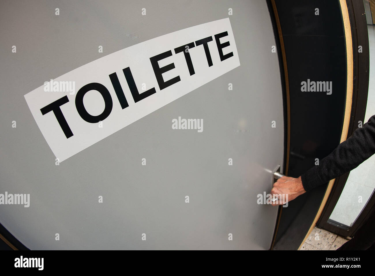 26 October 2018, Lower Saxony, Göttingen: 'Toilet' stands at the door of a unisex toilet or also All-Gender-Toilet in the school building. Two toilet rooms of the school, formerly one for boys and one for girls, were provided with the stroke 'Toilette' and prepared for the pupils, who do not find themselves in a classical gender order. Photo: Swen Pförtner/dpa - Stock Image