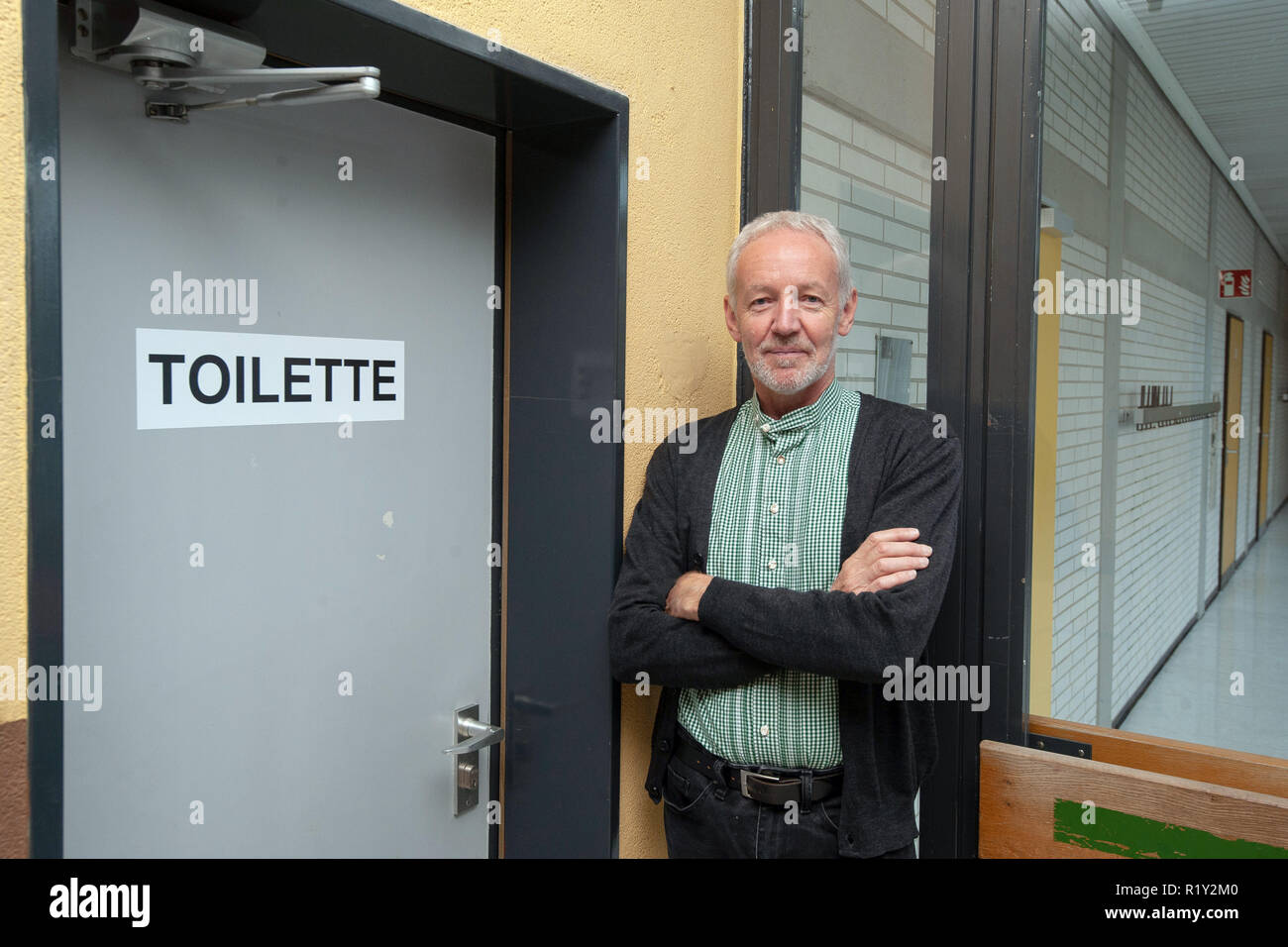 26 October 2018, Lower Saxony, Göttingen: Georg Bartelt, headmaster of the Hainberg-Gymnasium, is standing at the door of a unisex toilet or an all-gender toilet in the school building. Two toilet rooms of the school, formerly one for boys and one for girls, were provided with the stroke 'Toilette' and prepared for the pupils, who do not find themselves in a classical gender order. Photo: Swen Pförtner/dpa - Stock Image