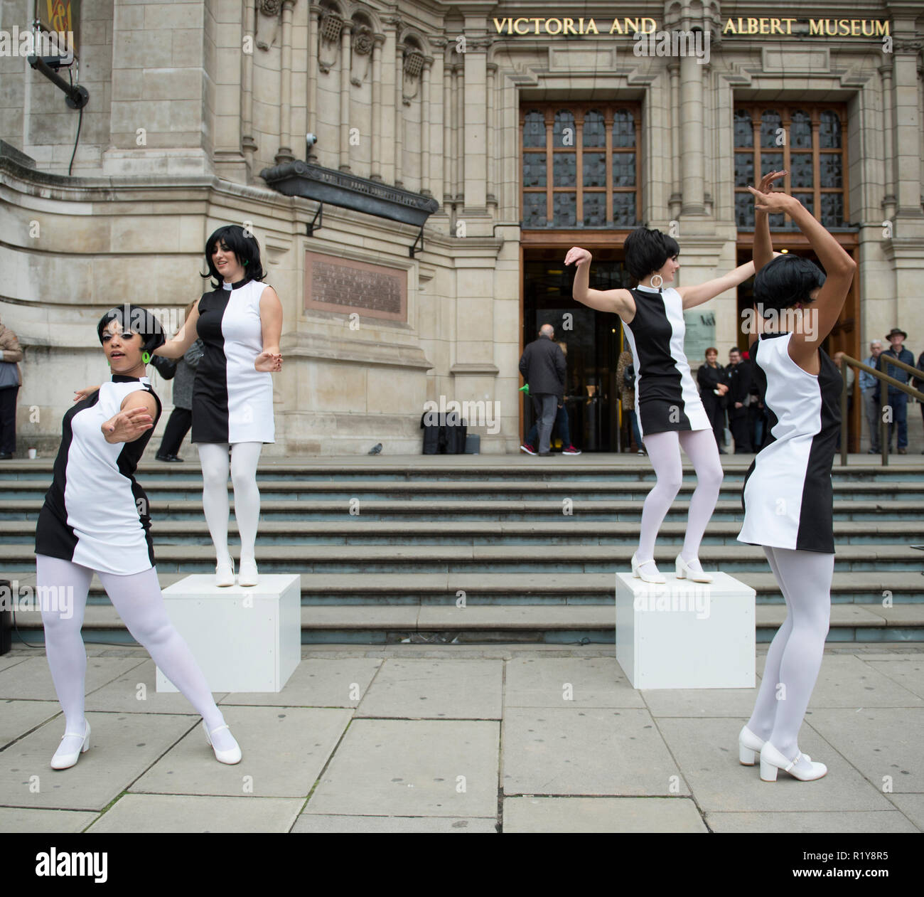 V&A, London, UK. 15 November, 2018. Models from the 1960s and 70s that worked with Mary Quant will gather alongside contemporary models to form a Quant revival. Meyer Dancers give a 60s Go-Go dance performance at the V&A entrance. The event marks the first time the public are able to purchase tickets for the Mary Quant exhibition opening at the V&A in 6 April 2019. Credit: Malcolm Park/Alamy Live News. - Stock Image