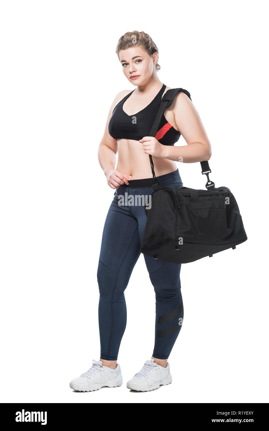 full length view of attractive young size plus woman with sports bag looking at camera isolated on white - Stock Image