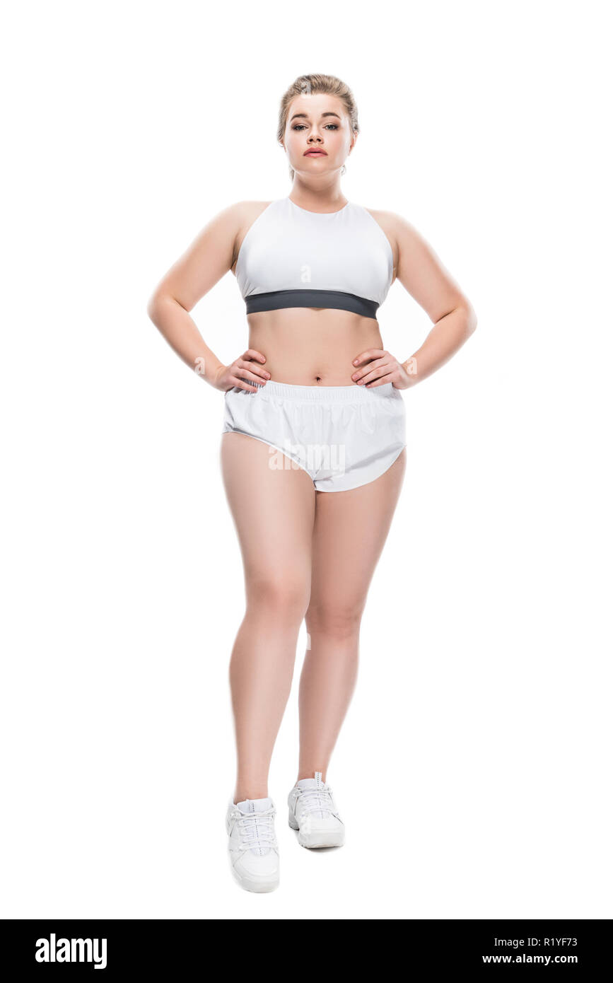 full length view of young size plus woman in sportswear standing with hands on waist and looking at camera isolated on white - Stock Image