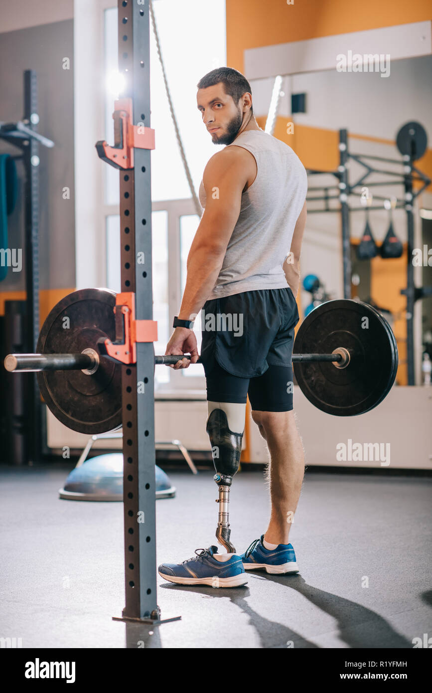 athletic sportsman with artificial leg working out with barbell at gym - Stock Image