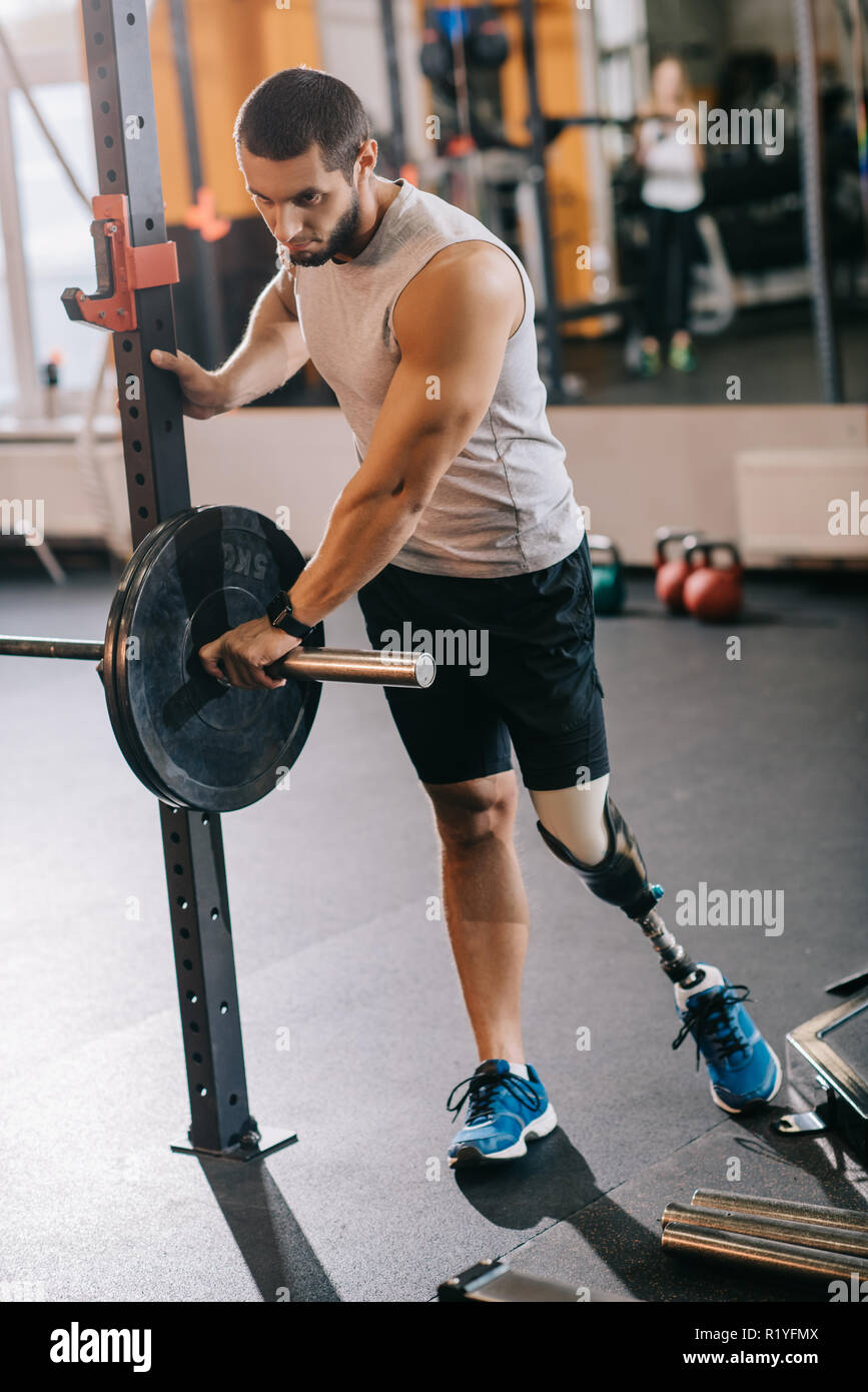 athletic young sportsman with artificial leg preparing for workout with barbell at gym - Stock Image
