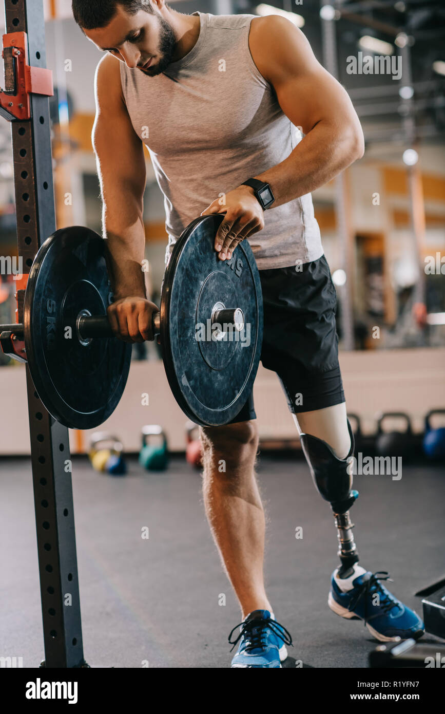 handsome young sportsman with artificial leg preparing for workout with barbell at gym - Stock Image