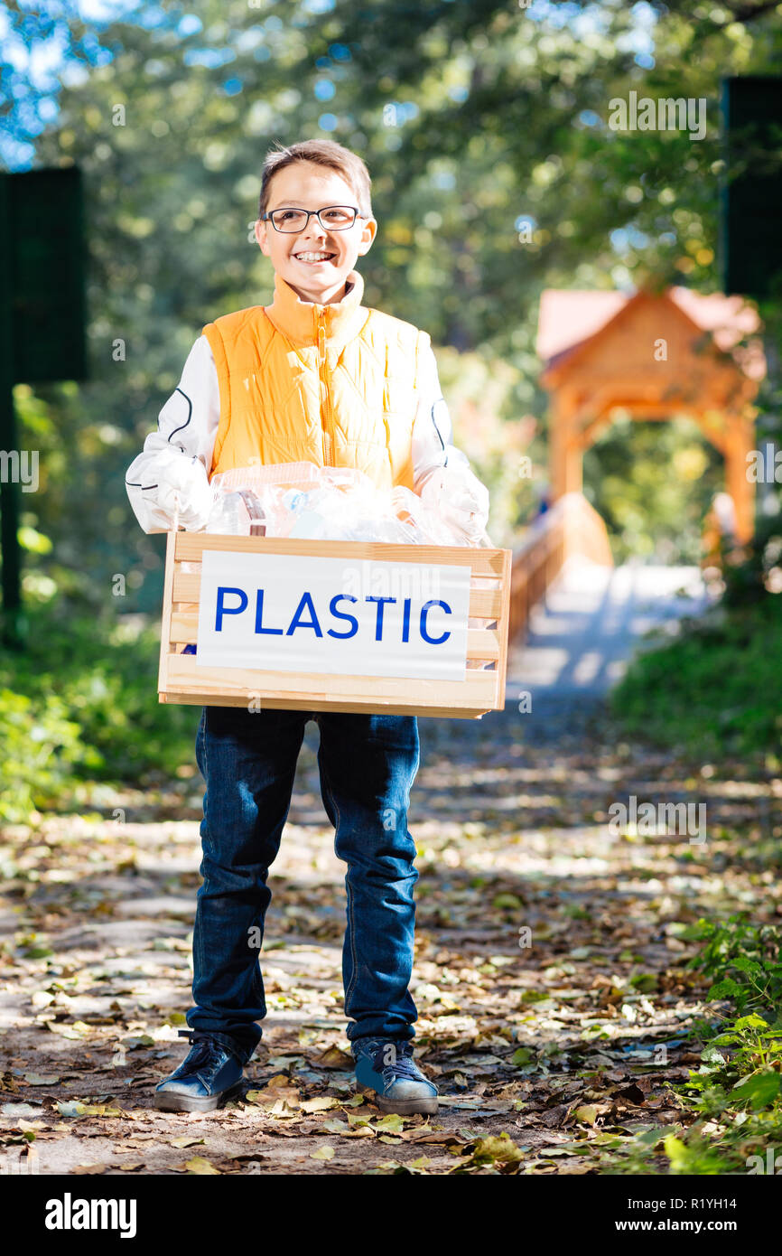 Delighted good looking boy helping the environment - Stock Image