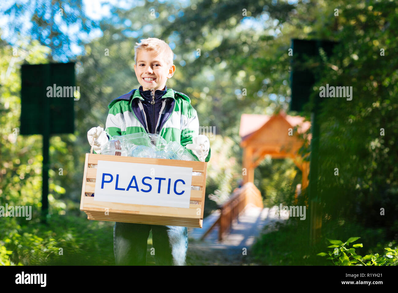 Cheerful cute boy cleaning the park from plastic - Stock Image