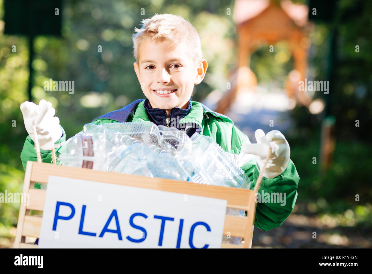 Cheerful blonde boy holding a box with bottles - Stock Image
