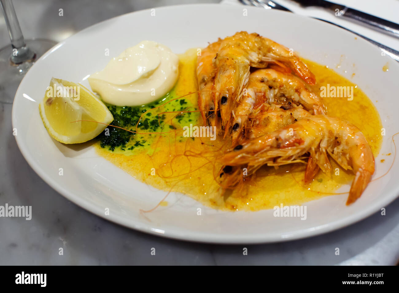 Nicely served prawns with lemon and souse in cafe - Stock Image