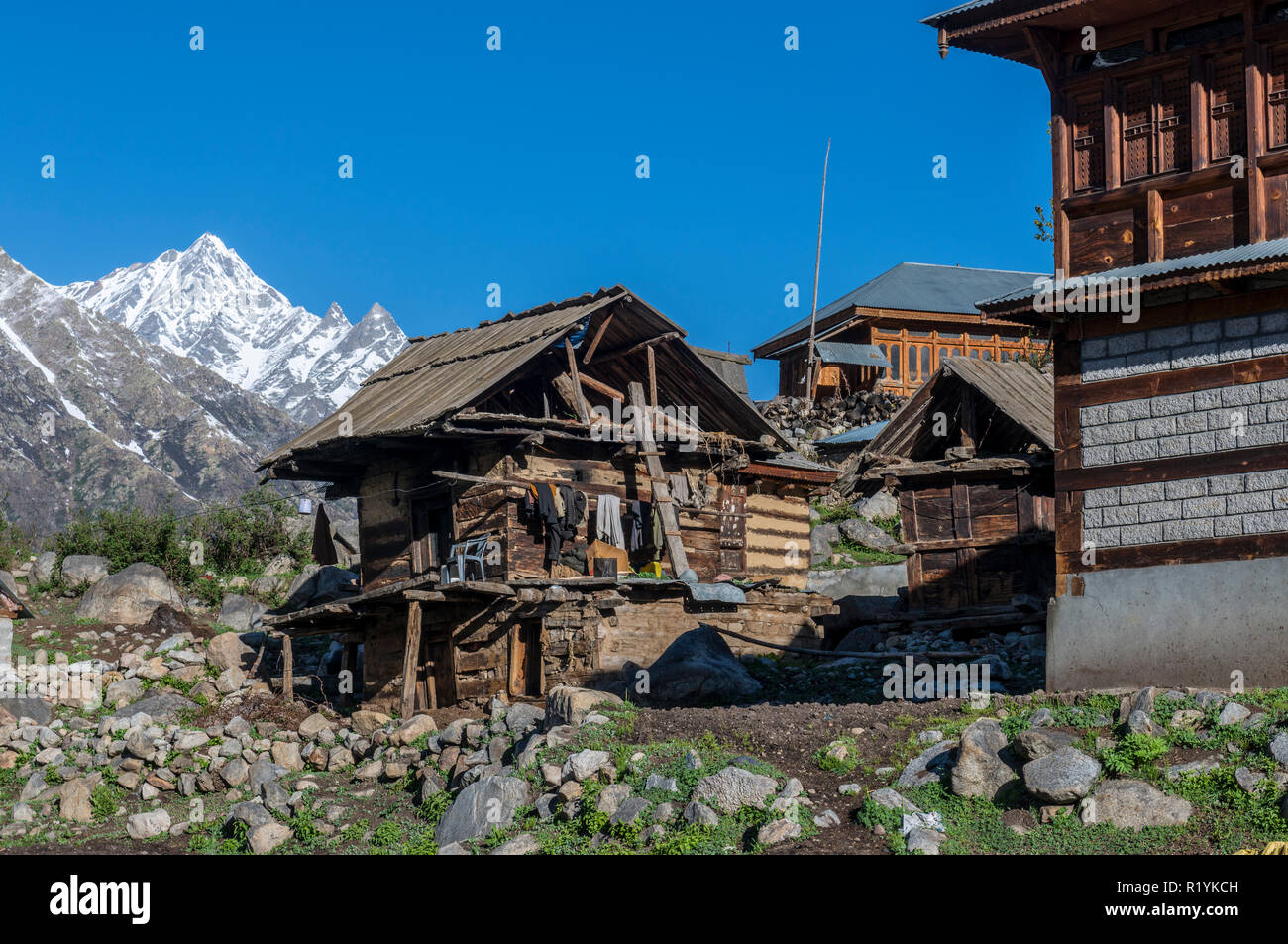 Wooden houses of Chitkul, the last village of Sangla Valley, located at 3.400 m and surounded by snow covered mountains Stock Photo