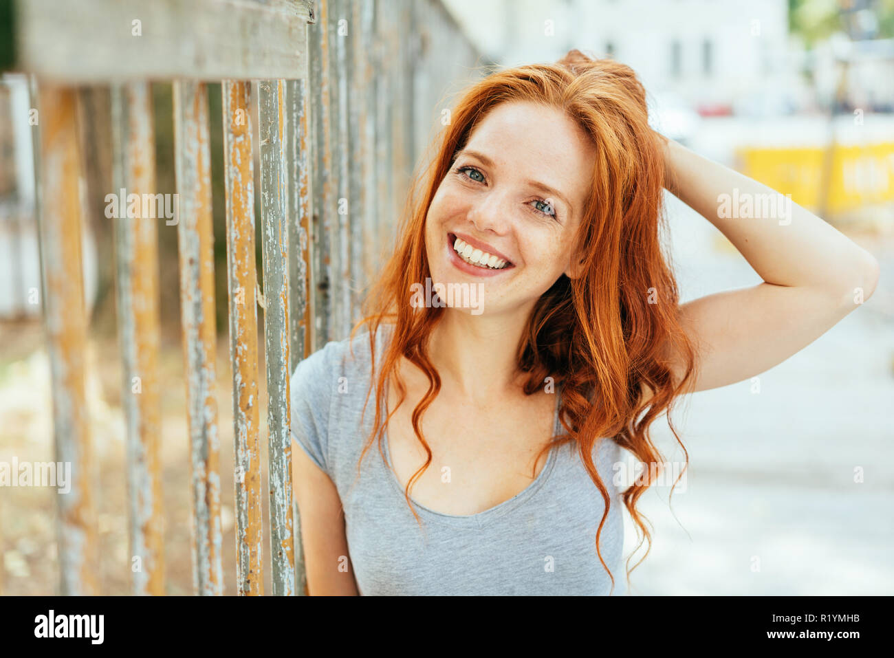attractive friendly woman with tousled long red hair standing against a metal railing in a high key outdoor street - Stock Image