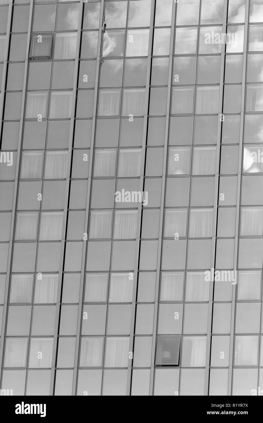 Glass facade background with blue sky reflection. Modern architecture and structure. Construction and design. Commercial property or real estate. Success and future concept. Stock Photo