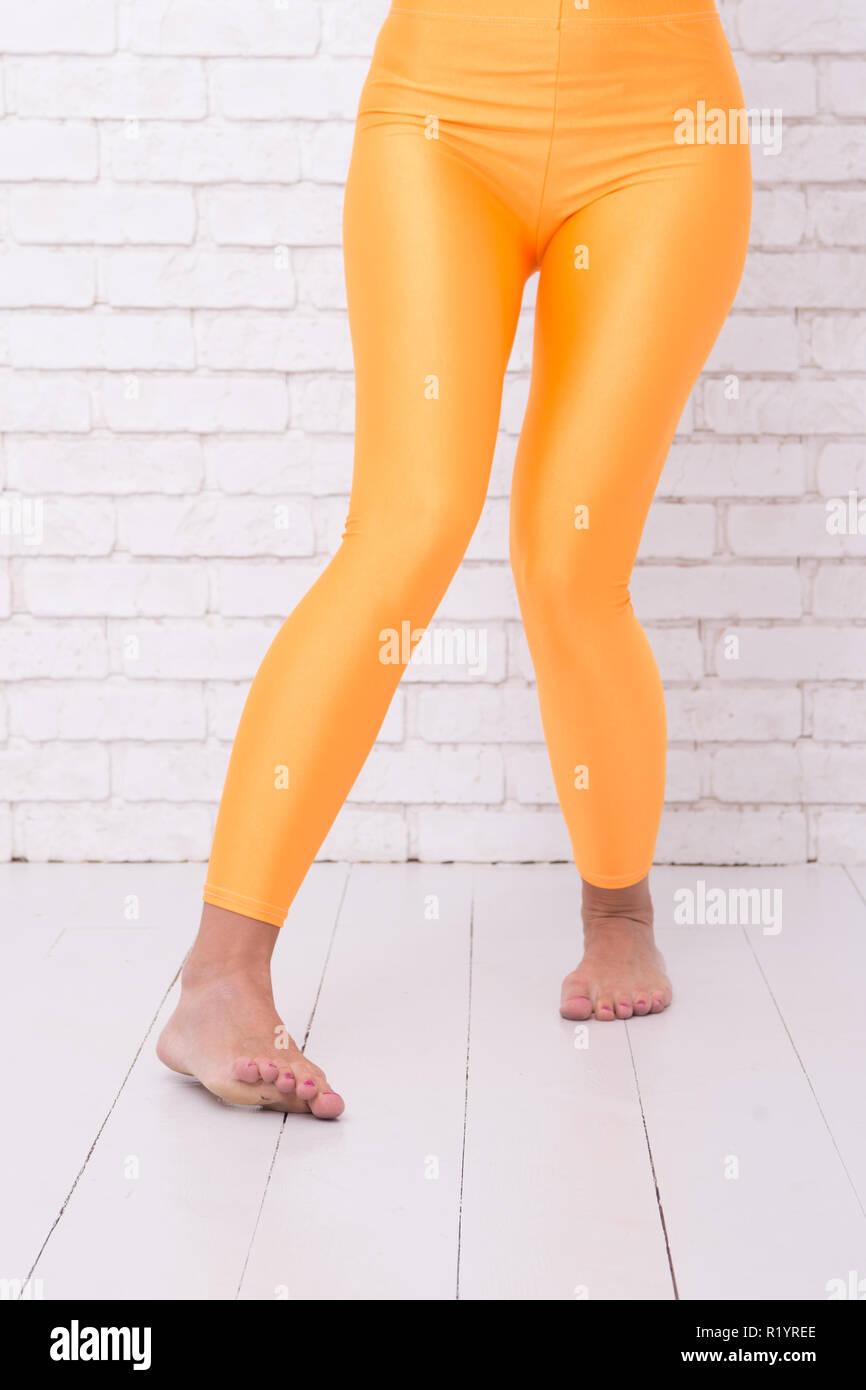 6e1d4a64a woman in orange leggings on legs. sport wear fashion. orange. practicing in  ballet studio. dancing ballet position of feet. a life full of Fun. going  crazy. ...