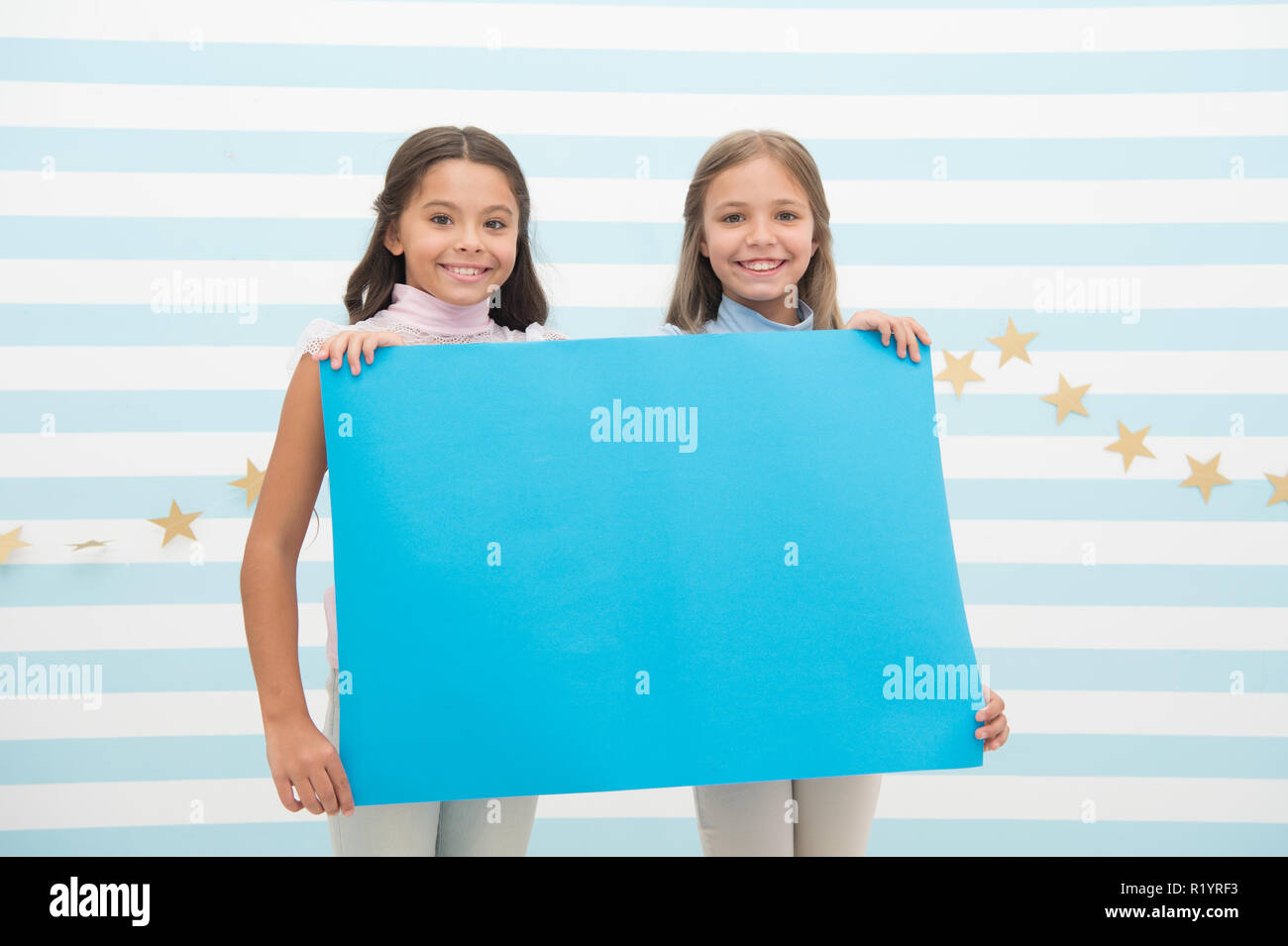 Kids announcement concept. Amazing surprising news. Girl hold announcement banner. Girls kids holding paper banner for announcement. Children happy with blank paper announcement copy space. - Stock Image