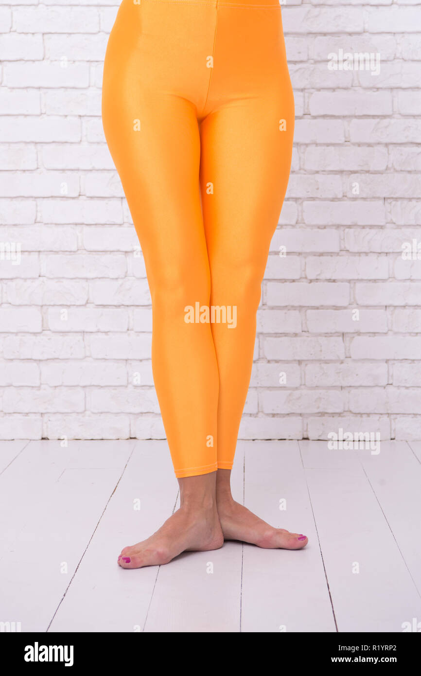 dancing ballet position of feet. orange. practicing in ballet studio. sport wear fashion. woman in orange leggings on legs. Adorn your Hobby with Dance. Good dance for Good Moments. dance your life - Stock Image