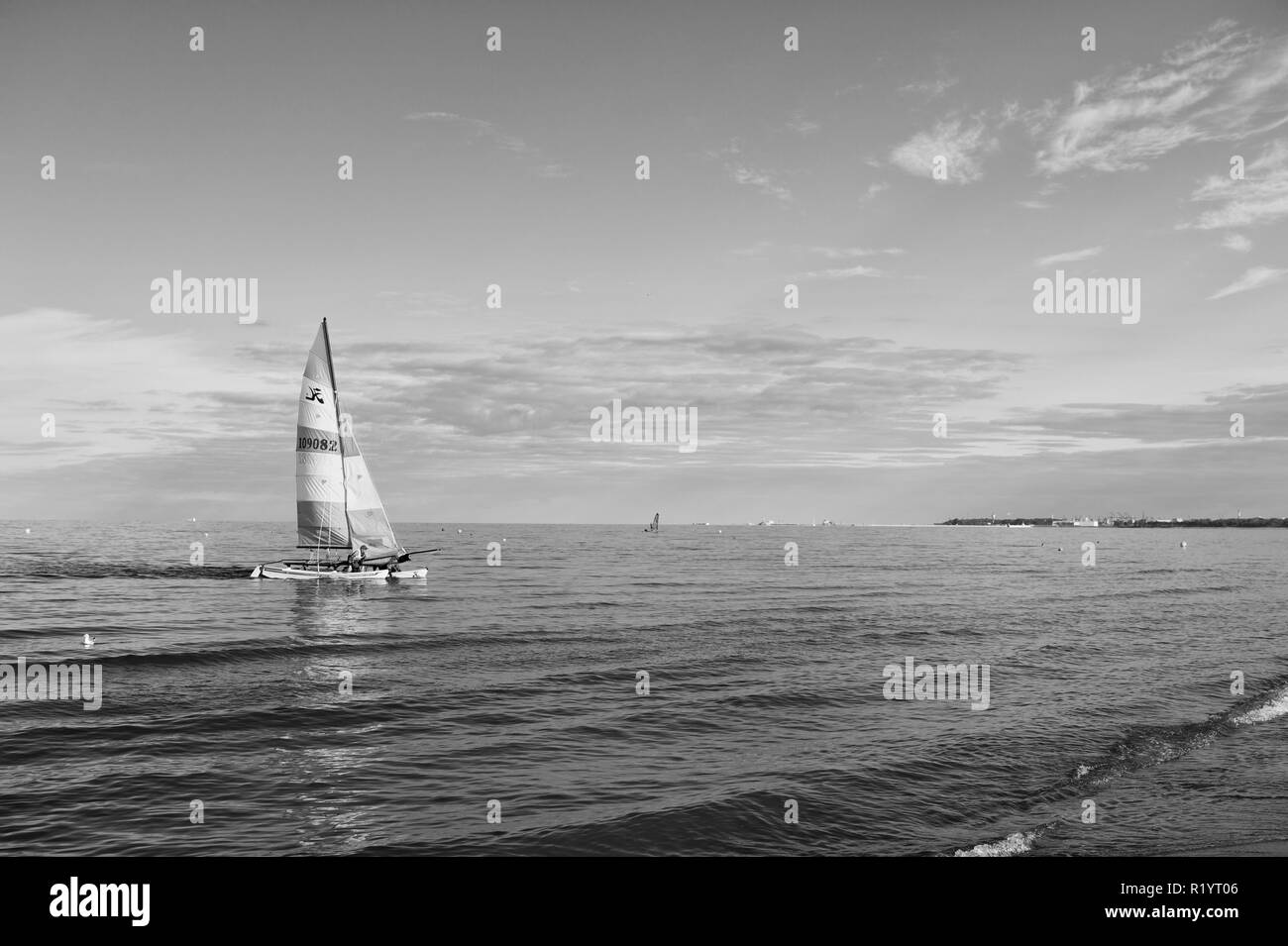 Gdansk, Poland-September 19, 2016 : Boat with bright sail sailing in sea of Gdansk, Poland. Sailboat on water on sunny blue sky. Summer adventure and active vacation. Yacht sailing - Stock Image