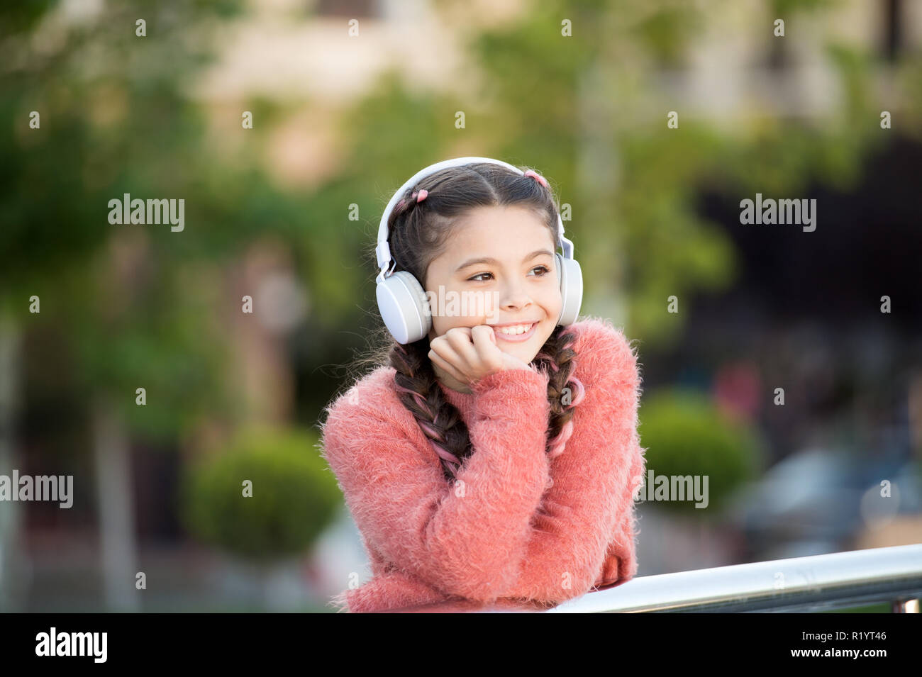 Funny cool stylish girl is listening to music and thinking about positiveness. Girl standing on the bridge with headphones. Tranquil influence of music. Nice girl in pink sweater enjoying song. - Stock Image