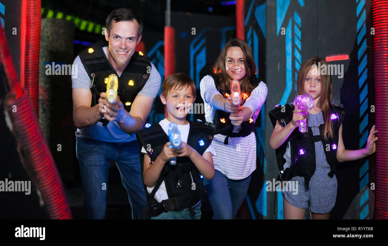 Group of happy kids and adults with laser guns having fun on dark