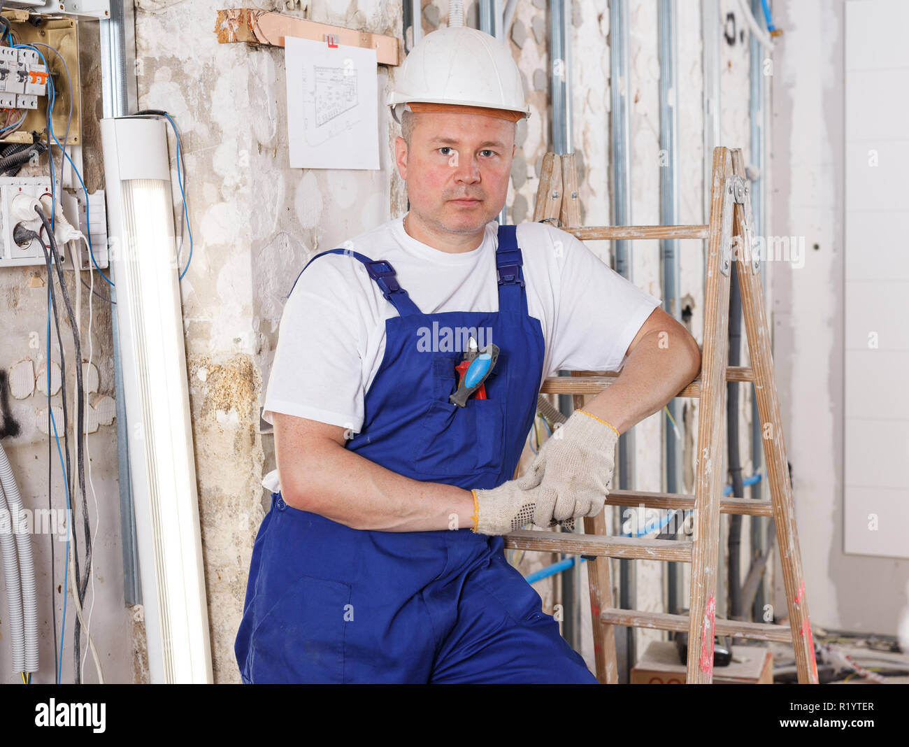 Portrait of confident professional builder posing in repairable room Stock Photo