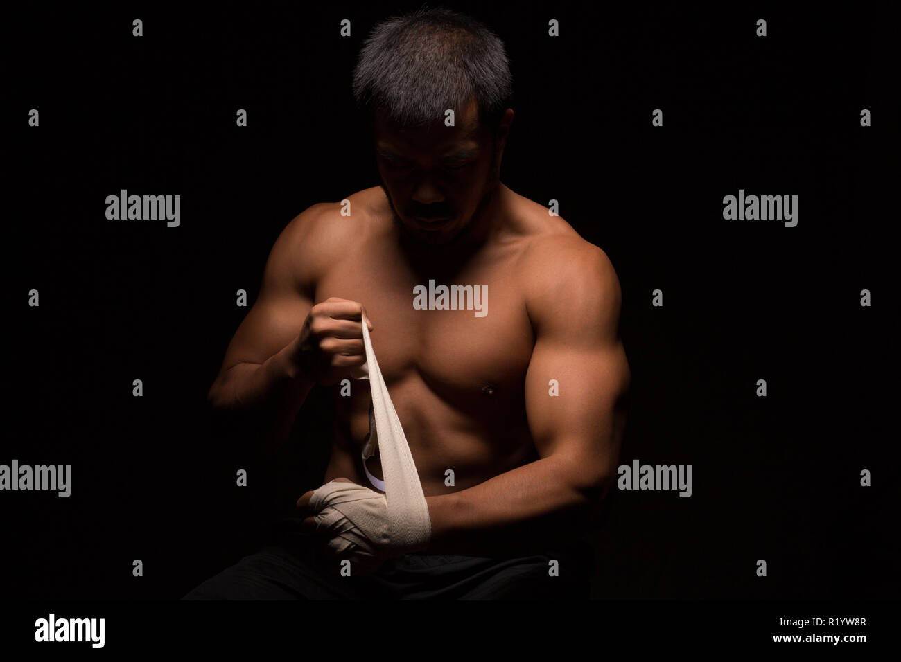 Asian man with muscular upper body is preparing for the fight - Stock Image