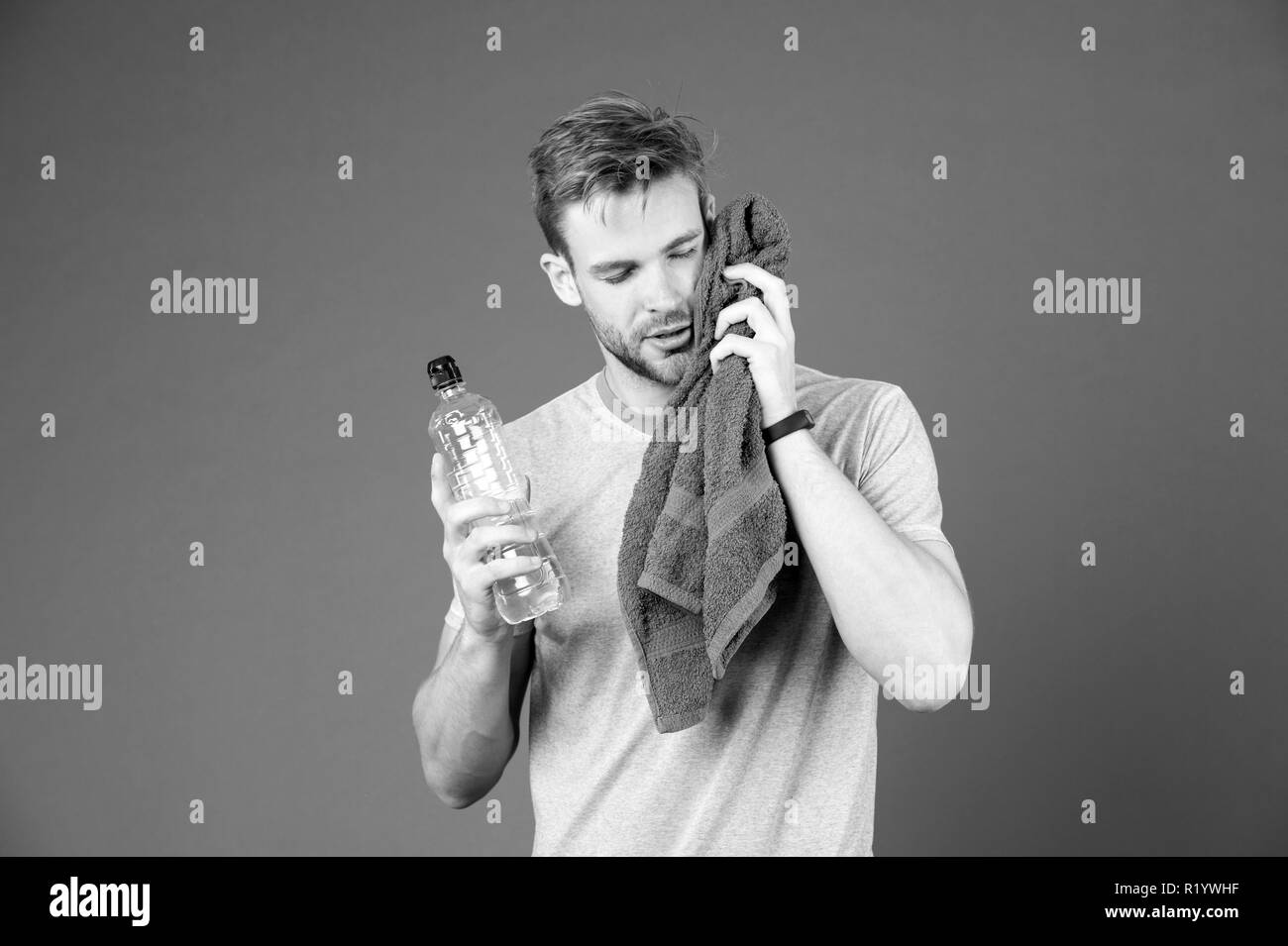 Athlete in blue tshirt and shorts with towel after training. Man hold water bottle on violet background. Sportsman with plastic bottle. Thirst and dehydration. Sport activity and energy. - Stock Image
