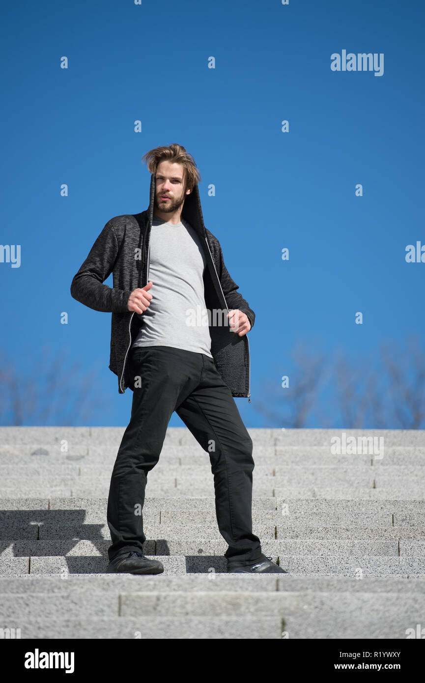 Steps concept. Young man in hooded sweatshirt stand on steps on sunny blue sky. Steps to success. The key to freedom is in the steps. - Stock Image